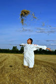 Girl in traditional Russian costume toss hay on a haystack — Stockfoto