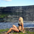 Girl in bikini sitting near a waterfall — Stock Photo