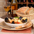 Bowl of seafood soup with wine and rustic bread — Stock Photo