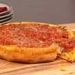 Chicago style deep dish pizza with a piece cut out - Stock Photo