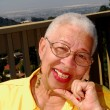Elderly African American woman sitting outdoors — Stock Photo