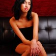 Attractive latino woman sitting on a couch — Stock Photo