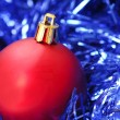 Red Christmas ornament on blue garland — Stock Photo #5979443