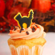 Royalty-Free Stock Photo: Halloween cupcake with fall foliage