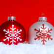 Two Christmas ornaments in snow — Stock Photo