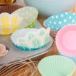 Variety of cupcake liners with wire whisk — Stock Photo