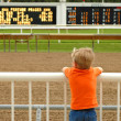 Young boy waiting for horses at race track — Stock Photo