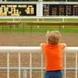 Young boy waiting for horses at race track - Stock Photo