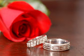 Two wedding rings with a red rose on a table — Stok fotoğraf
