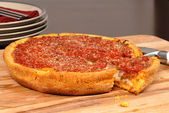 Chicago style deep dish pizza with a piece cut out — Stock Photo