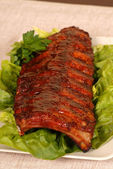 Slab of ribs resting on lettuce — Stock Photo