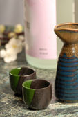 Japanese sake setup with flowers in background — Stock Photo
