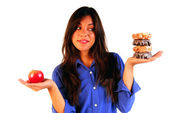 Young woman deciding betwen apple or donuts — Stock Photo