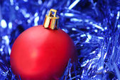 Red Christmas ornament on blue garland — Stock Photo
