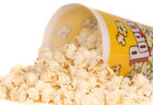 Container of popcorn with popcorn spilling out — Stock Photo