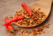 Red chili peppers and red pepper flakes on a spoon — Stock Photo