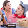 Drunk man with his wife in traditional dresses - Stock Photo