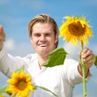 Blond man sunflower sky field — Stock Photo