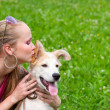 Girl kissing puppy - Stock Photo
