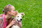 Girl kissing puppy — Stock Photo