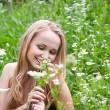 Young girl in a meadow with camomiles - Stock Photo
