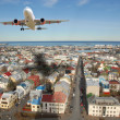 Aircraft above city - Stock Photo
