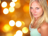Beautiful blond girl with shimmering blur background — Stock Photo
