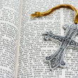 Open bible with a silver cross — Stock Photo