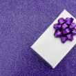 A silver present with bow on purple background — Stock Photo