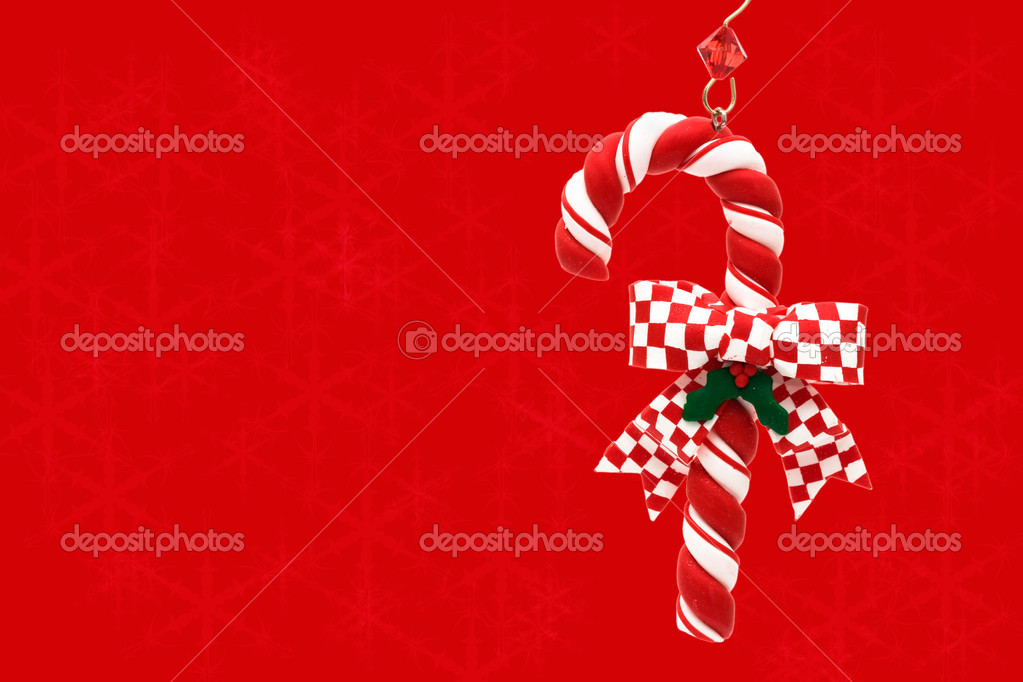 A candy cane hanging on a red snowflake background, Christmas Time — Zdjęcie stockowe #6326418
