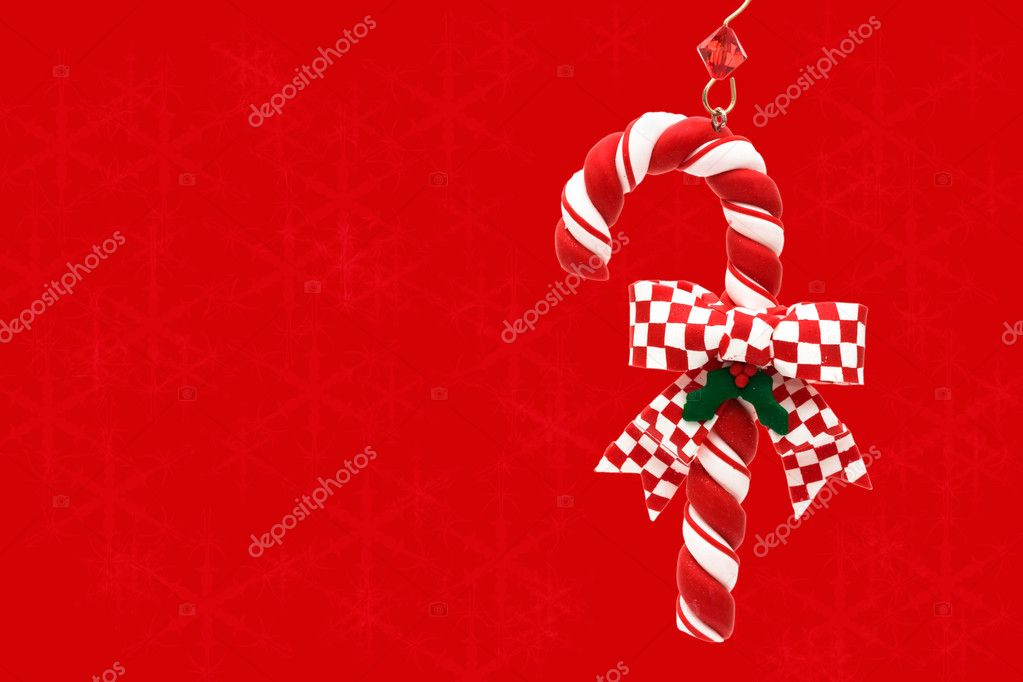 A candy cane hanging on a red snowflake background, Christmas Time — Foto de Stock   #6326418