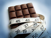 Chocolate and tape measure — Stock Photo