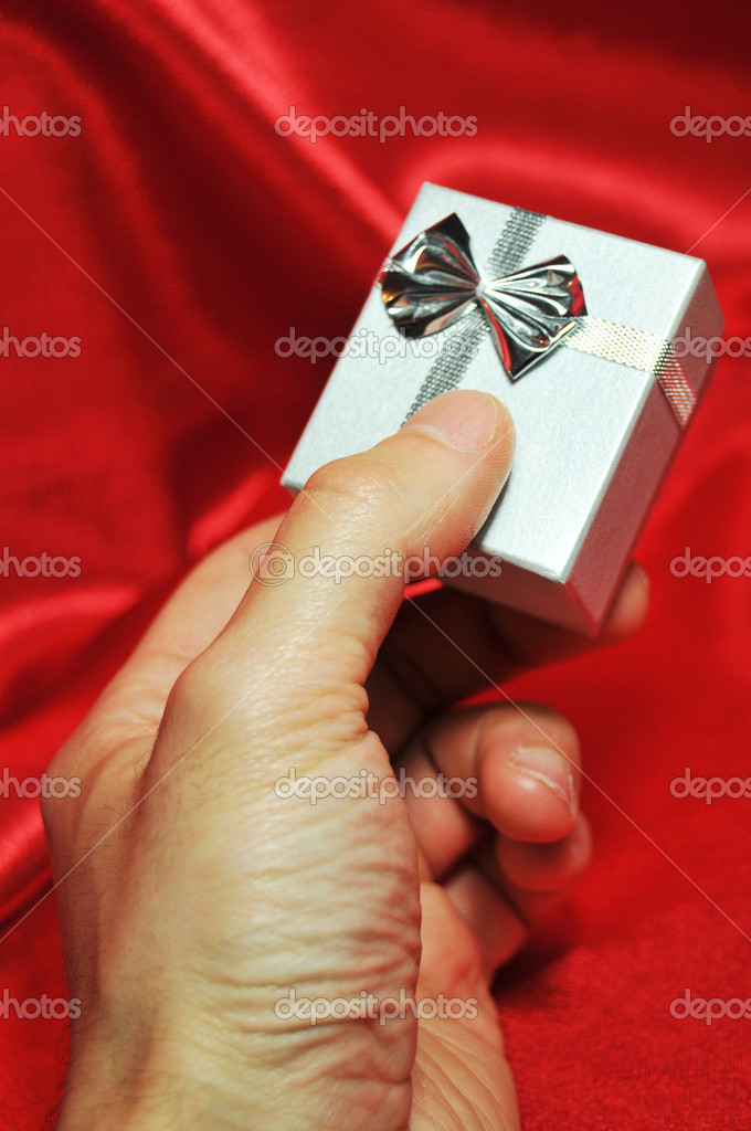 Hand holding beautiful gift box on red silk background — Stock Photo #6639435