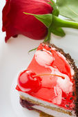 A piece of cake and a red rose — Stock Photo