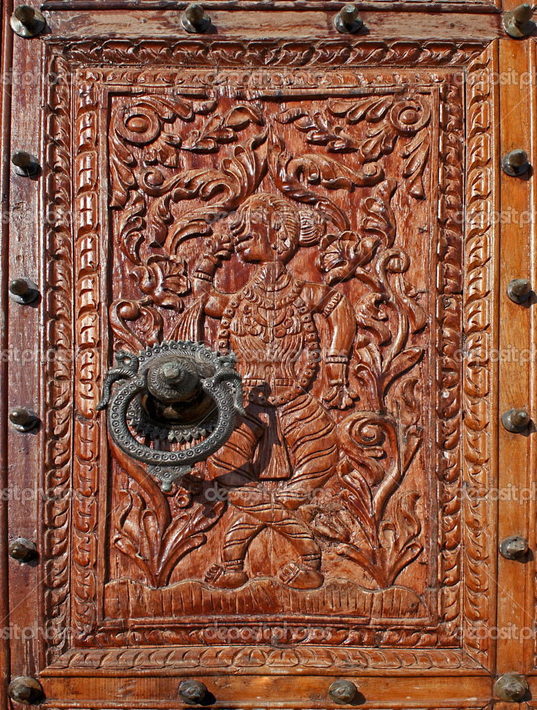 Low relief carved wood with a beautiful metal knocker