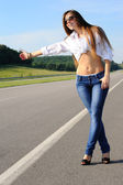 Girl hitchhiking on the road — Stock Photo