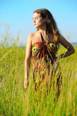 Girl in colorful sun-dress in grass — Stock Photo