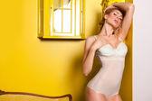 Beautiful woman posing in a yellow interior — Stock Photo