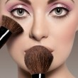 Portrait of a beautiful woman with a make up brush — Stock Photo