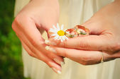 Wedding rings on hands of the bride on a camoline — Stock Photo