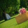 Stock Photo: Wedding rose bouquet on a basket and Newlywed Couple in nature