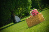 Wedding rose bouquet on a basket and Newlywed Couple in nature — Stock Photo