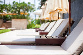Plank beds with umbrellas in a sunny day — Foto Stock