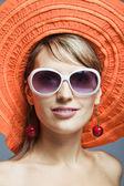 Beautiful girl in orange hat and sunglasses — Stock Photo