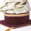 Stock Photo: Master's cap with dollars