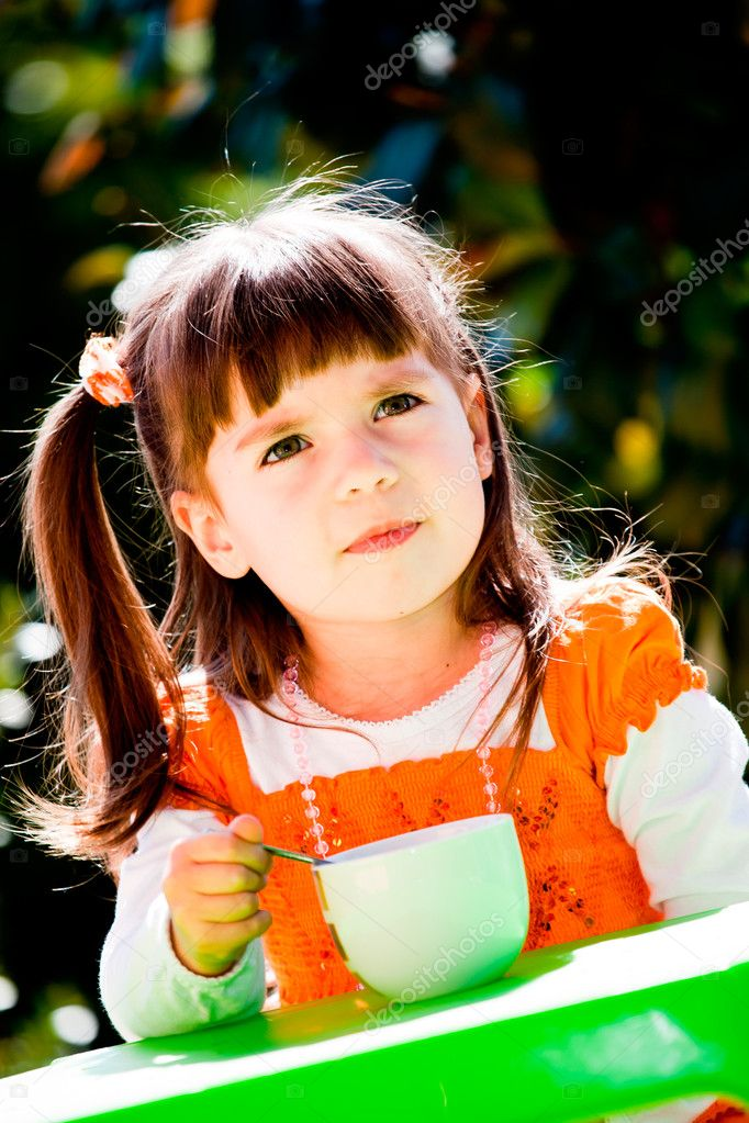 Girl eating yoghurt in the garden — Stock Photo #6032674