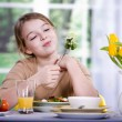 Young girl eating salad at home. A studio shoot — Stock Photo