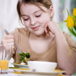 Stock Photo: Young girl eating salad at home. studio shoot