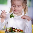 Young girl eating salad at home. A studio shoot — Stock Photo #6098589