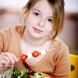 Young girl eating salad at home. A studio shoot — Stock fotografie